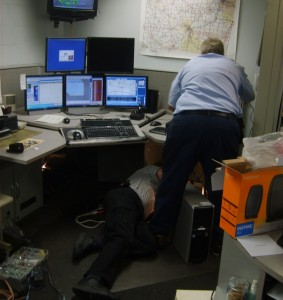 Chip and Rick from Mobilcomm work on installing new dispatch consoles at BCSO